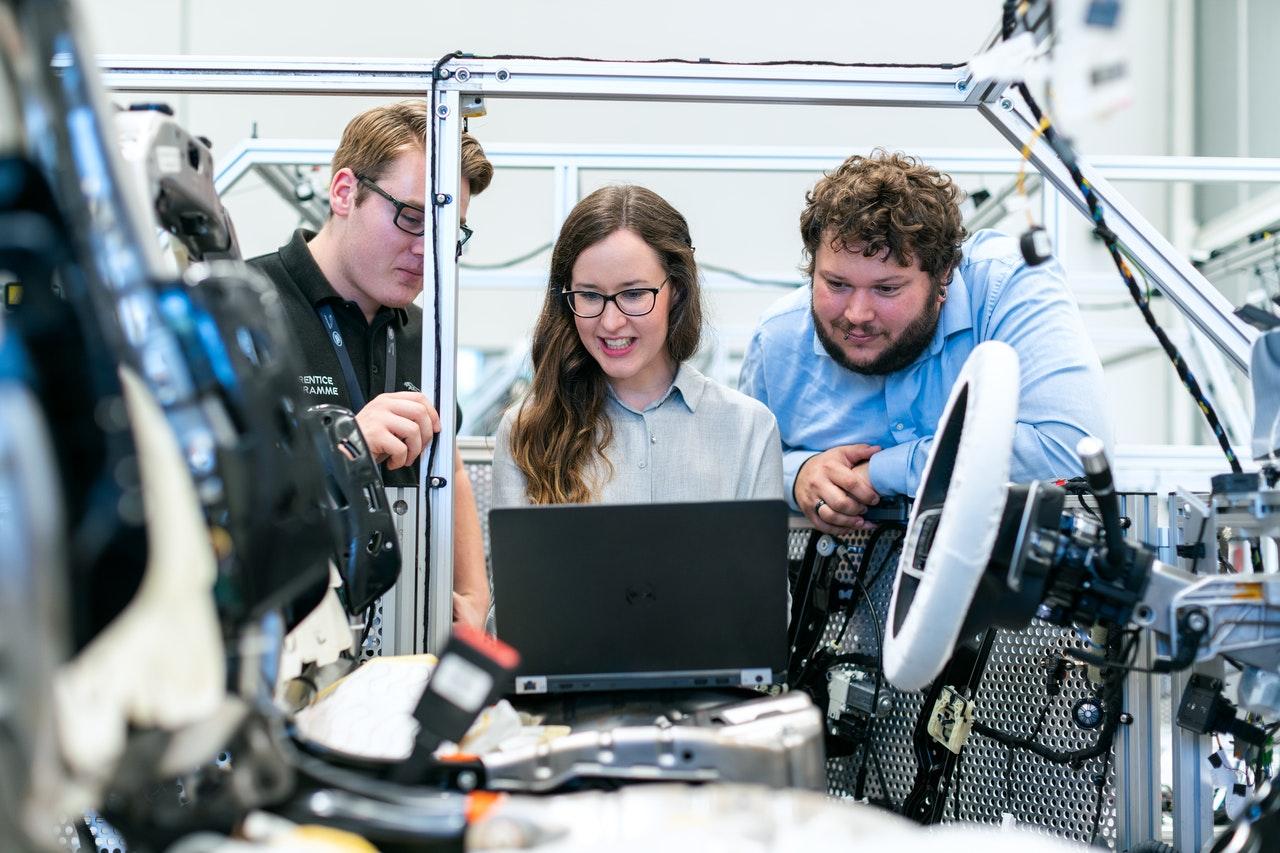 three engineers using robotics in factory